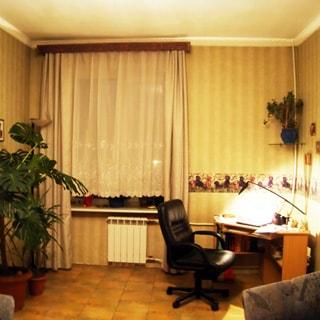 На фото: часть помещения жилой комнаты, одно окно, под окном - радиатор батареи центрального отопления, слева от окна на полу в горках - комнатные декоративные растения, справ от окна в углу - письменный стол с офисным креслом, стены оклеены обоями, полы - линолеум