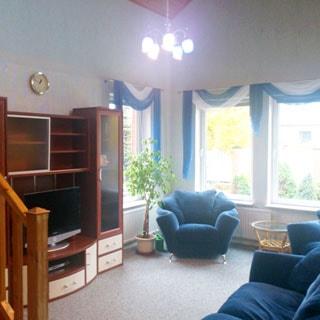 На фото: внутреннее помещение - гостиная, шкаф-стенка с телевизором, мягкая мебель, три окна, лестница на второй этаж
