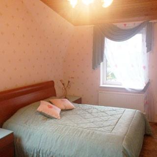 На фото: внутреннее помещение - спальня, разноуровневый потолок, двуспальная застеленная кровать, две прикроватные тумбочки, окно