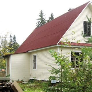 На фото: жилой одноэтажный дом, двускатная крыша, фасад облицован сайдингом, входной тамбур, перед домом газон, деревья