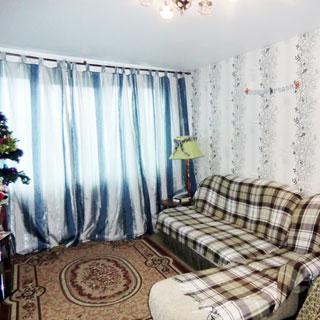 На фото: часть жилой комнаты с окном, окно закрыто шторой, стены оклеены обоями, на полу - ковер, у стены справа от окна - мягкий диван, журнальный столик, торшер