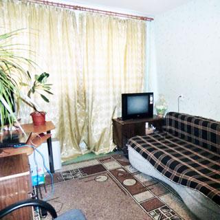 На фото: часть жилой комнаты с окном, окно закрыто шторой, стены оклеены обоями, пол - линолеум, у стены справа от окна - диван, тумба, телевизор, слева от окна - компьютерный столик