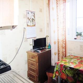 На фото: кухня, окно со стеклопакетом, плита - газовая, у окна тумба с телевизором, обеденный стол, табурет, стены оклеены обоями