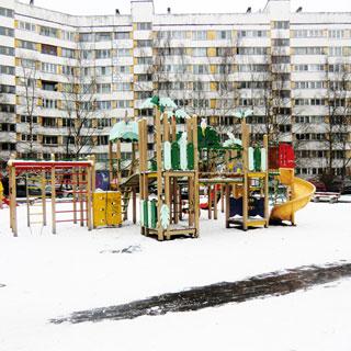 На зимнем фото: дворовая территория с оборудованной детской площадкой, на заднем плане - деревья, припаркованные у дома автомобили