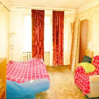 Однокомнатная квартира 30 кв.м на Витебском проспекте (Московский, МО-45, Гагаринское) продается. Комната 17.0 кв.м с выходом на балкон На фото: часть помещения жилой комнаты, слева у стены - разложенный мягкий диван-кровать, левее - комод, справа у стены - мягкое кресло, стул, стены оклеены обоями, полы - паркет