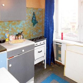 На фото: часть помещения кухни, большое окно, под окном - радиатор центрального отопления, слева от кона вдоль стены - двухкомфорочная газовая плита с духовым шкафом, левее - тумба-стол, над ней - навесная полка-шкаф