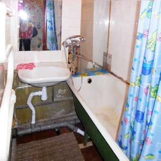 На фото: часть помещения ванной комнаты, прямо у стены - керамическая раковина, над раковиной - зеркало, слева на стене - полотенцесушитель, справа - ванная, смеситель общий для ванны и раковины, стены облицованы керамической плиткой