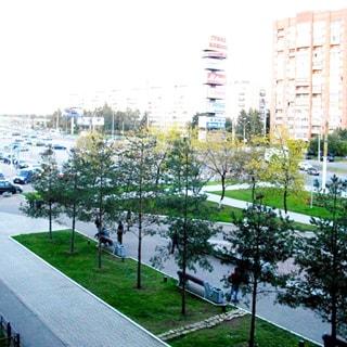 На фото: вид из окна на проспект, благоустроенная придомовая территория, практически первращенная в сквер, газоны, деревья, вымощенные тротуарным камнем пешеходные дорожки, на дальнем плане - проезжая часть проспекта с проезжающими и припаркованными автомобилями