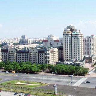 На фото: вид с высоты на жилой квартал, современные жилые дома в окружении просторных тротуаров с деревьями и газонами, шестиполосная проезжая часть с разделительным газоном, на проежей части и на парковках - легковые автомобили