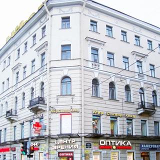 На фото: часть фасада пятиэтажного кирпичного многоквартирного жилого дома с угла, фасад классического стиля оштукатурен, на третьем этаже - балконы, в цоуольном и первом этаже - коммерческие помещения, магазины, по фасаду - вывески