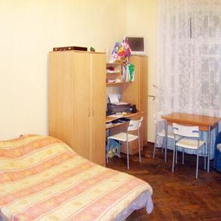 На фото: часть помещения жилой комнаты, одно окно, у окна - письменный стол, два стула, слева от окна в углу - одностворчатый шкаф, левее - компьютерный стол с навесными полками, левее - двустворчатый шкаф, левее - двуспальный диван-кровать, полы - паркет