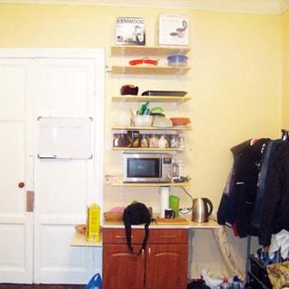 На фото: часть помещения жилой комнаты, двустворчатая входная дверь, справа от двери - кухонный стол-тумба, над ним - навесные полки, на нижней полке - микроволновая печь, справа в углу - вешалка для одежды, полы - паркет