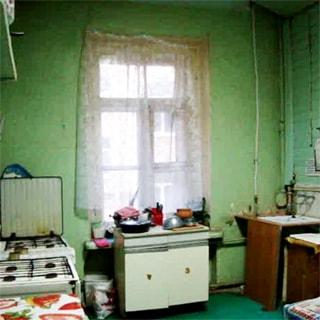 На фото: часть помещения кухни, одно двустворчатое окно, у окна - тумба-стол, справа в углу - металлическая эмалированная мойка, правее - тумба-стол и навесные полки, слева от окна у левой стены две газовые четырехкомфорочные плиты, тумба-стол, навесные полки