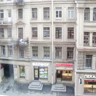 На фото: вид из окна на улицу, напротив - часть фасада кирпичного дома, фасад оштукатурен, есть балконы, в цокольном этаже - коммерческие помещения, магазины, по фасаду - вывески, видна часть тротуара и арка во двор
