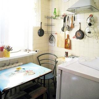На фото: часть помещения кухни, одно двустворчатое окно, под окном - батарея центрального отопления, у окна - стол, стул, табурет, у правой стены - газовая плита, над ней - вытяжка, на стене - навесные полки, справа от входа - холодильник, стены облицованы керамической плиткой