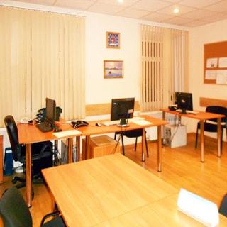На фото: часть офисного помещения, два окна, на окнах - вертикальные жалюзи, офисная мебель, компьютеры, стены - окрашены, потолки - подвесные, на потолке - точечные светильники, полы - ламинат