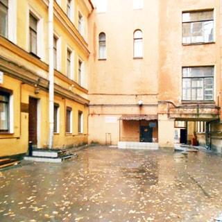На фото: фасад кирпичного многоэтажного дома со стороны двора, фасад оштукатурен и окрашен, без балконов и декора, слева - вход в парадную со ступеньками вверх, прямо - вход в полуподвальное помещение со ступеньками вниз под козырьком, дворовая территория асфальтирована, справа впереди - арка в следующий двор