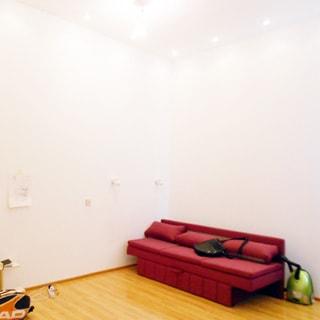 На фото: часть помещения, полы - ламинат, стены и потолок окрашены в белый цвет, на потолке - точечные светильники, в углу - мягкий диван-кровать, справа от него на полу - пылесос