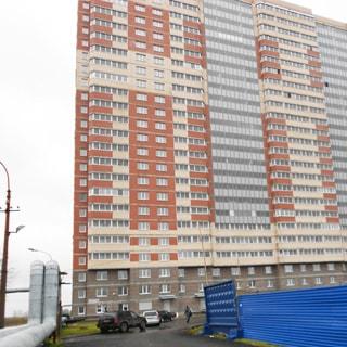 На фото: часть фасада многоэтажного жилого дома, лоджии и балконы застеклены, перед домом асфальтированный проезд, слева от проезда воздушная теплотрасса, справа - синий забор соседней стройки, перед домом припаркованные автомобили