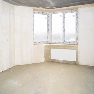 На фото: помещение жилой комнаты под чистовую отделку, одно трехстворчатое угловое окно, установлен стеклопакет, под окном - батарея центрального отопления, стены оштукатурены, полы - цементно-песчаная стяжка
