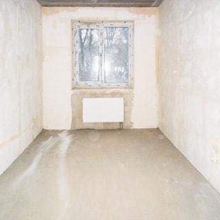 На фото: помещение жилой комнаты под чистовую отделку, одно двустворчатое окно, установлен стеклопакет, под окном - батарея центрального отопления, стены оштукатурены, полы - цементно-песчаная стяжка
