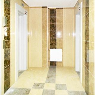 На фото: помещение лифтового холла, четыре лифта, стены и полы отделаны керамической плиткой, прямо у стены - батарея центрального отопления