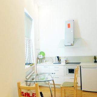 На фото: часть помещения кухонного типа, слева - одно окно, у окна обеденный столик со стеклянной столешницей, у стола - два стула, прямо у стены - кухонные столы-тумбы, небольшой холодильник, варочная электрическая поверхность, над ней - вытяжка, слева в углу - мойка со смесителем, полы - ламинат, стены - окрашены в белый цвет