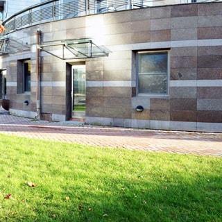 На фото: часть фасада цокольного этажа дома, фасад облицован керамо-гранитной плиткой, стеклянная входная дверь в помещение на уровне пола, над дверью светопрозрачный козырек на металлическом каркасе, справа от двери - окно в помещение, территория перед домом вымощена тротуарным камнем, устроен газон