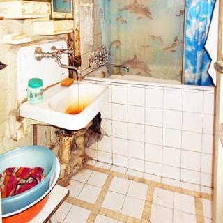 На фото: часть помещения ванной комнаты, прямо у стены - ванная со смесителем, слева от нее - керамическая раковина на кронштейнах со своим смесителем, полы и стены у ванной облицованы керамической плиткой