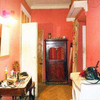 На фото: часть помещения прихожей, прямо у стены - шкаф, слева в углу - открытая дверь, слева у стены - столик и зеркало над ним, справа у стены - стиральная машина, полы - паркет