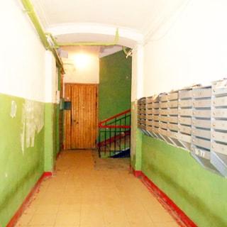 На фото: помещение лестничной клетки первого этажа, справа на стене - сблокированные почтовые ящики, прямо впереди - лестница с металлическими перилами, полы - керамическая плитка, стены - окрашены не в полную высоту