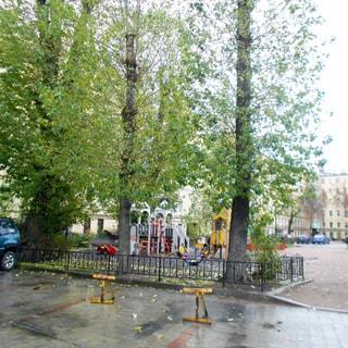 На фото: часть дворовой территории, оборудованная детская площадка, огороженный газон, деревья, остальная территория вымощена тротуарным камнем, припаркованы автомобили