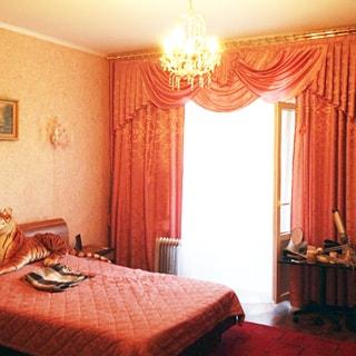 На фото: часть помещения жилой комнаты - спальни, окно с открытой балконной дверью, слева у стены - двуспальная кровать, у кровати - прикроватная тумбочка, справа у окна - туалетный столик на колесиках, на стене - светильник, на потолке - люстра