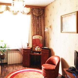 На фото: часть помещения жилой комнаты, окно, под окном - радиатор батареи центрального отопления, справа от окна в углу - двухтумбовый туалетный столик с зеркалом, над столом на стене - светильник, справа от стола - стул, еще правее - тумба с телевизором, на стене - картина в раме, стены оклеены обоями, на потолке - люстра