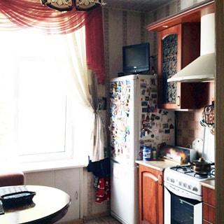 На фото: часть помещения кухни, окно, слева от окна - обеденный стол и кухонный мягкий уголок, справа от окна вдоль стены - двухкамерный холодильник, на нем - небольшой телевизор, кухонная тумба-стол, над ней - навесной кухонный шкаф, правее - четырехкомфорочная газовая плита с духовым шкафом, над ней - вытяжка, правее - еще одна кухонная тумба-стол