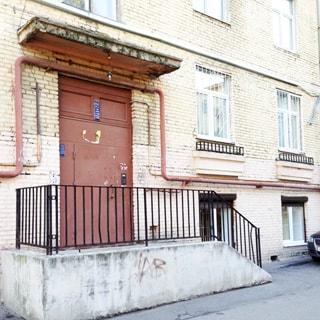 На фото: часть фасада жилого кирпичного дома со стороны двора, вход в парадную, ступеньки, металлические перила, козырек, металлическая входная дверь в парадную, домофон, у дома припаркован легковой автомобиль