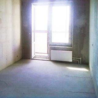 На фото: часть жилого помещения, окно с открытой балконной дверью, установлен стеклопакет, состояние помещения - под чистовую отделку, пол - цементно-песчаная стяжка