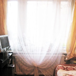На фото: часть помещения жилой комнаты, большое трехстворчатое окно, под окном - батарея центрального отопления, слева от окна - компьютерный столик, на столе - монитеор компьютера, справа от окна у стены - диван-кровать
