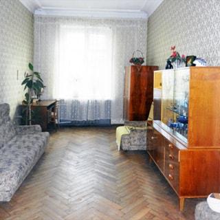 На фото: часть помещения жилой комнаты, одно окно, слева от окна у стены - письменный стол со стулом, диван, справа от окна - шкаф, кресло, сервант, стены оклеены обоями, пол - паркет