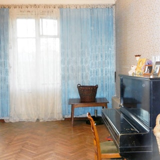 На фото: часть помещения жилой комнаты, одно окно, справа у окна - журнальный столик, справа у стены - пианино со стулом, стены оклеены обоями, пол - паркет