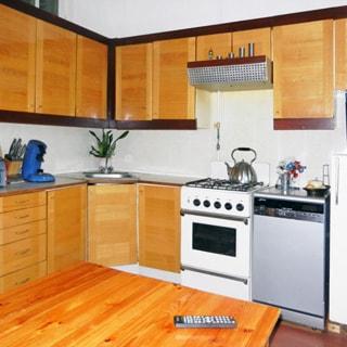 На фото: часть помещения кухни, в центре - угловая металлическая мойка со смесителем, справа и слева - кухонные столы-тумбы и навесные шкафы, в правой секции - четырехкомфорочная газовая плита с духовым шкафом, над плитой - вытяжка, правее посудомоечная машина и холодильник, на переднем плане - обеденный стол