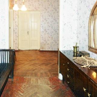 На фото: часть помещения коридора и прихожей, слева у стены - деревянная скамья, справа у стены - комод, над ним на стене - зеркало, на дальнем плане - двери в соседние помещения, на потолке - люстра, стены оклеены обоями, пол - паркет