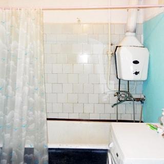 На фото: часть помещения ванной комнаты, впереди у стены - ванная со смесителем и газовой колонкой, справа у стены - стиральная машина, стена у ванной облицована керамической плиткой, стена справа - окрашена