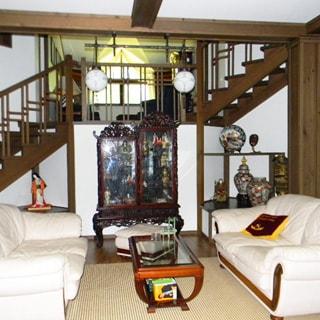 На фото: часть помещения большой комнаты или зала, посреди комнаты - журнальный столик, справа и слева от него - мягкие диваны, потолок с деревянными балками на деревянных колоннах, на балках - люстры, на дальнем плане вдоль стены - лестница на следующие уровни