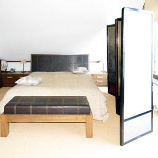На фото: часть жилого помещения - спальни в мансардном этаже, посреди помещения - двуспальная кровать, слева у стены - тумбы и шкафы для одежды, справа - окно, между окном и кроватью - ширма