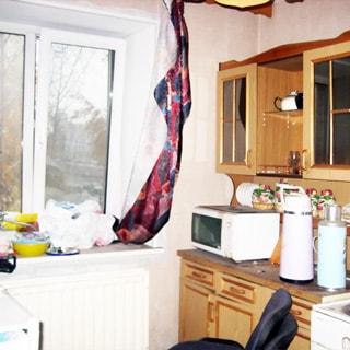 На фото: часть помещения кухни, окно, под окном - радиатор батареи центрального отопления, справа от окна в доль стены - кухонный гарнитур из тумб и навесных шкафов, справа выглядывает угол электрической кухонной плиты с духовым шкафом
