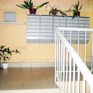 На фото: часть помещения парадной со стороны входа, лестница с металлическими перилами с деревянной накладкой, полы и ступени облицованы керамической плиткой, стены - окрашенный кирпич, прямо на стене - блок почтовых ящиков