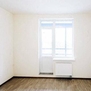 На фото: часть помещения комнаты, окно с балконной дверью, под окном - радиатор батареи центрального отопления, белые стены и потолок, полы - ламинат, комната пустая, без мебели