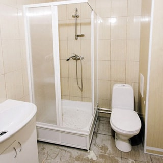 На фото: часть помещения совмещенного санузла, прямо в углу - душевая кабина, слева от нее - керамическая раковина на тумбе белого цвета с дверцами, справа - унитаз-компакт, стены облицованы керамической плиткой, полы - плитка