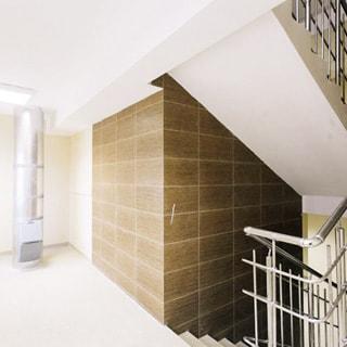 На фото: часть помещения лестничой площадки, впереди слева - мусоропровод, справа - лестничные марши вверх и вниз, перила из нержавеющей стали, стены лифтовой шахты облицованы керамической плиткой